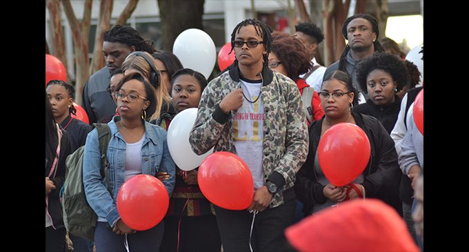 Vigil honors student as police look for suspect